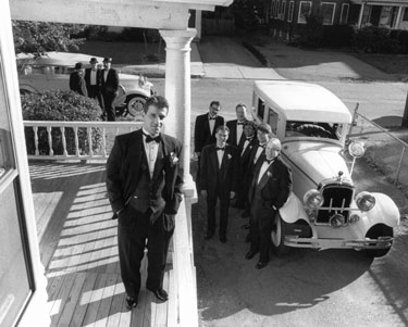 groom and groomsmen with antique cars